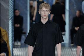 Miuccia Prada繼續在她的系列中探尋性別設計。他將男裝單品融入女裝元素。輕外套和箱型短袖襯衫都非常受歡迎,服裝的面料為黑色尼龍,同時,工裝式外套,襯衫和西裝套裝都非常摩登優雅,服裝運用暗色色調,比如黑色,藍色和灰色。優質西裝為系列注入了新穎元素--雙排扣西裝突出了6個紐扣設計,管形西裝和外套給人以年輕感和摩登感。