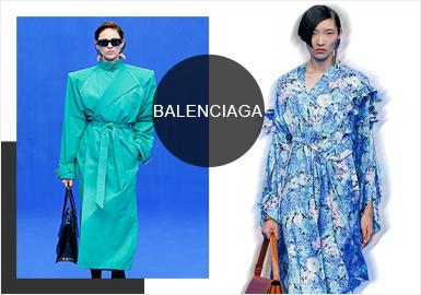 "Balenciaga 2020春夏系列以 "" New fashion uniforms ""为主题,灵感源自职场着装,秀场被一片蓝色包裹着,嘉宾围绕着中心排列成圆形而坐,严谨的蓝色调、圆形围绕式座位让形形色色的职场场景缓缓而来,本季以对西装外套的解构作为开场,开衫、风衣与裙装等形式陆续出现。前几季火热的袜靴也在本季回归,垂坠感的印花长裙、宽肩造型,表现出女性强大的力量。但怪趣味设计以不可忽略存在的巨大裙摆、Oversize 轮廓等让整个系列精英与怪诞共存。"