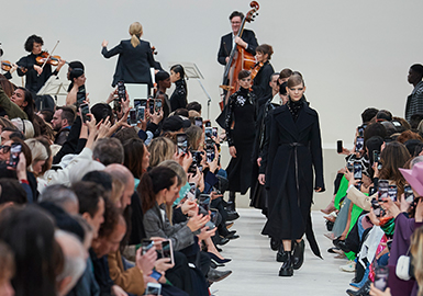 在这个系列中,不同身形的男女模特,穿上大量的黑、灰和贯穿品牌的经典Valentino红与低沉靛蓝、祖母绿等,从基本轮廓出发,衬托出精准剪裁的力道。在成衣系列依旧展现高定技术的Valentino,这次无疑是比前几季来得低调,但细节的处理依旧展现出不遑多让的实力。系列中穿插了写实的花卉图样,以刺绣、印花等手法,勾勒出花朵傲然绽放的美丽身姿,为本是沉静平稳的大衣外套、无袖连身裙平添几分生气。