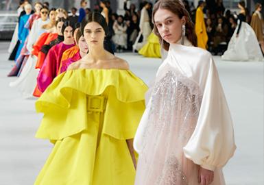 2020/21秋冬,随着派对季进入高潮,礼服造型将大放异彩。从柔和量感到极简紧身等一系列版型的直筒礼服长裙和干练西装打造出成熟而性感的基调。重点应用以冬季暗色调为主的浓郁调色板。黑色回归并成为关键色彩,广泛运用于所有礼服造型类别,同时以珍贵宝石色和暖调金属色做为装饰性强调色。年代感基调和奢华浪漫主义成为重要主题。通过柔美的荷叶边领线和修长端庄的垂坠曲线强调出年代幻想风格。采用纹理细节来强调本季盛行的女性气质。新维多利亚风格引起更多的关注,呈现出蕾丝、薄纱叠层和饱和天鹅绒等造型。