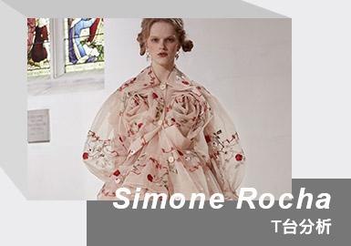 "Simone Rocha 由华裔爱尔兰设计师于2010年创建的个人同名设计师品牌。设计师擅于运用刺绣、珍珠等元素营造浪漫华丽氛围。2021/22秋冬系列于伦敦海德公园圣约翰教堂发布,以""冬日玫瑰""为主题,描述""公主的叛逆且不为人知的脆弱""。不同于春夏系列的仙甜,本季更新叛逆朋克主义甜酷路线。繁复的网纱、褶皱、立体玫瑰、手工刺绣与荷叶边元素,融入黑色皮革夹克硬朗衣着风格,塑造散发酷飒反叛气质的复古文艺少女形象,充分表现了新生代设计师的大胆和前卫。"