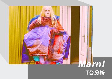 意大利奢侈品牌 Marni  21/22秋冬系列 是创意总监Francesco Risso在封锁期间创作的第二个系列。Francesco Risso于2016年加入Marni,2020 年底与Marni 续约,继续担任品牌创意总监一职。该系列 结合多元化的设计元素,丰富灵动的色彩,经典的时装轮廓,摆脱了固有的规则,极富个性的同时又十分浪漫。Marni 21/22秋冬系列相当于是一首颂歌,颂扬了时装进程中最能被感知亲昵浪漫主义,为我们的日常寻觅全新的意义。本系列廓形与色彩,戏剧化的明暗对比,给人以强烈视觉冲击,表达着对浪漫主义的追求。秀场前几天创意总监Francesco Risso就通过邮件和媒体套近乎邀请一起用餐,一起通过Zoom、意大利国家时装商会官网和腾讯中国等数字化方式和Marni 一起互动。